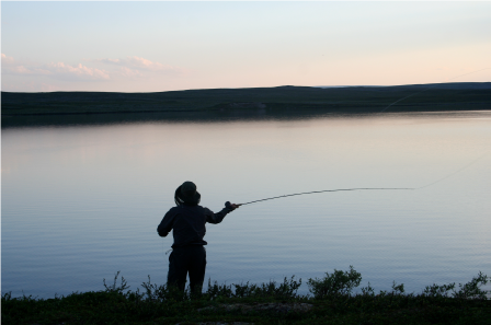 person standing in front of a body of water with a fishing reel