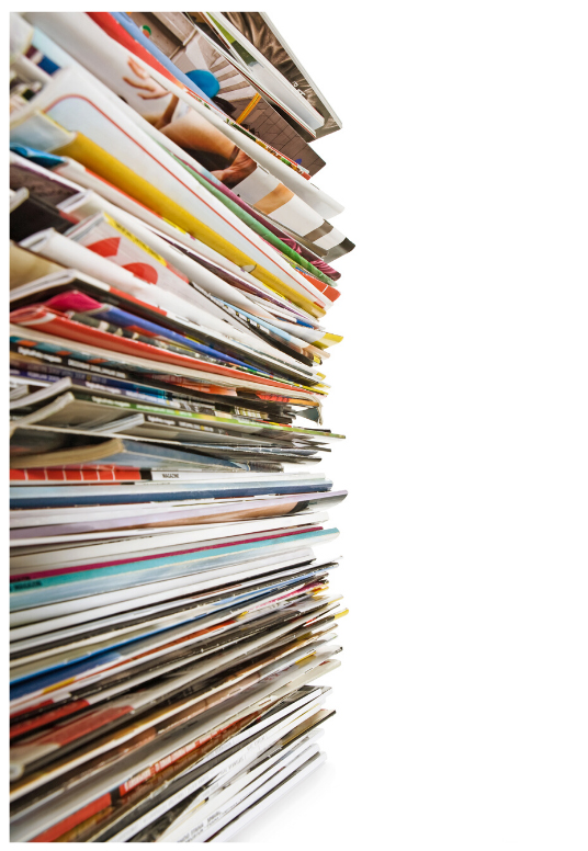 Photo of a stack of magazines with their spines facing out.