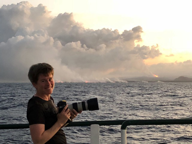 Jackie Caplan-Auerbach on the 2018 research cruise offshore Kilauea with lava flowing into the water visible behind her.