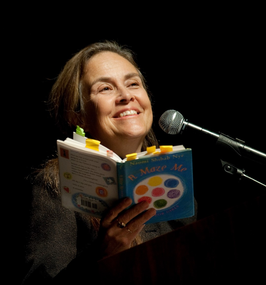 Photo of author Naomi Shihab Nye positioned behind a microphone and holding a book