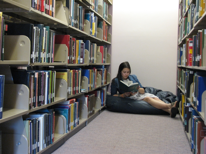 Photo of student reading a book in the stacks