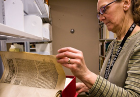 Photo of Special Collections manager, Tamara Belts, handling a rare book.