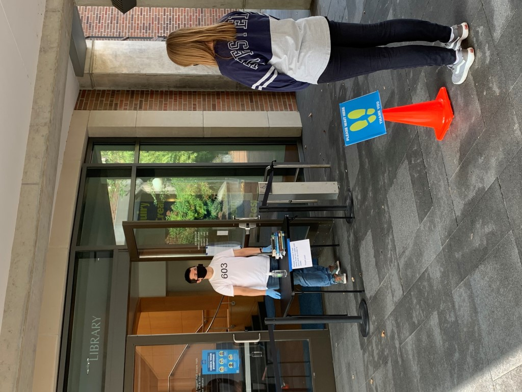 2 people standing outside beneath library skybridge for on-site pickup services