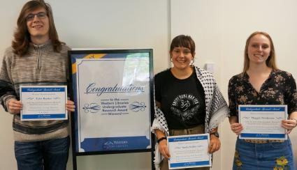 """Three people standing near a """"Congratulations"""" sign whole holding awards certificates for the Libraries Undergraduate Research Award"""