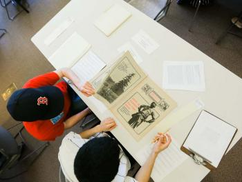 Students examining copies of the local alternative newsletter Northwest Passage at the Archives Building.
