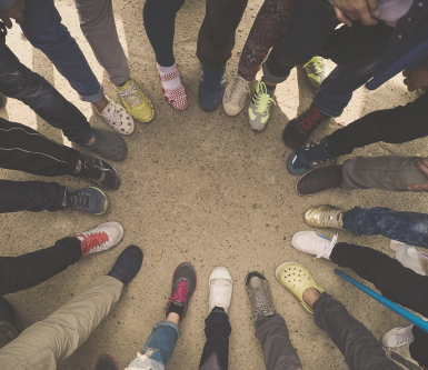 Aerial view looking downward at people standing in a circle with only the shoes and legs of the people in the circle visible