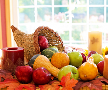 Cornucopia with apples and squash inside and on the surrounding leaf-covered surface, near several un-lit candles.