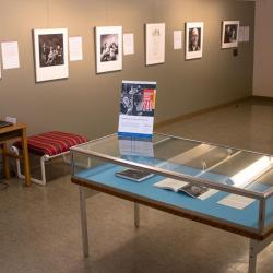 Gallery including table case showing images from the exhibit